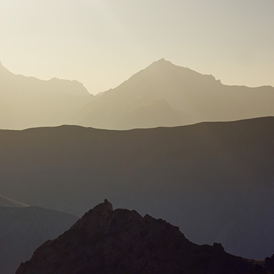 background layered mountain peaks at sunset